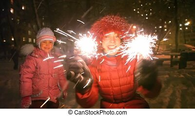 young woman with sparkler, near little girl, night outdoor