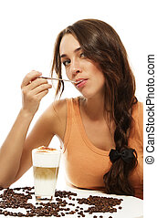 young woman with spoon in her mouth sitting at a table wit latte macchiato coffee on white background