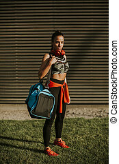 Young woman with sport bag outdoor