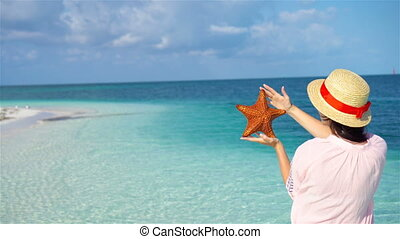 Young woman with starfish on white beach in the nature reserve
