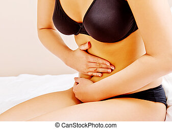Young woman with stomach ache kneeling on bed
