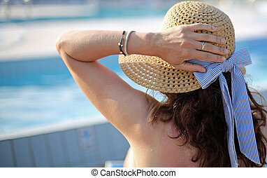 woman with straw hat at the pool of luxury resort