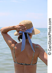 woman with straw hat at the sea