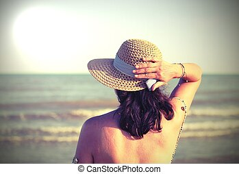 young woman with straw hat by the sea