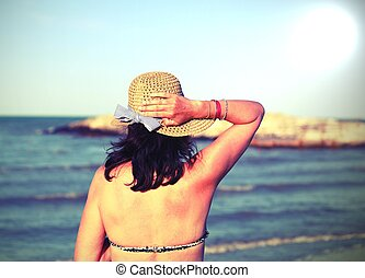 young woman with straw hat in summer