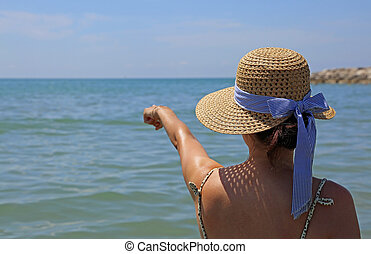 woman with straw hat shows hand in the horizon of the sea