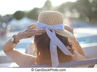 Young woman with straw hat sunbathing in the exclusive resort on