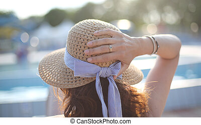 Young woman with straw hat sunbathing in the luxurious resort on