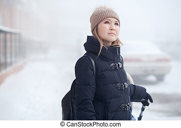 Young woman with stroller walking in winter, looks thoughtfully at sky.