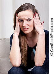 Young woman with strong migraine