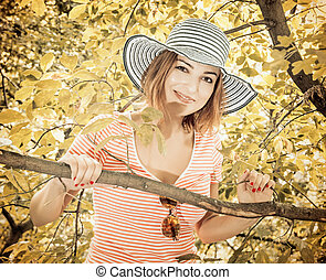 Young woman with stylish sunhat posing on tree, vintage filter