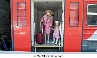 Young woman with suitcase and her little daughter leaves the train car