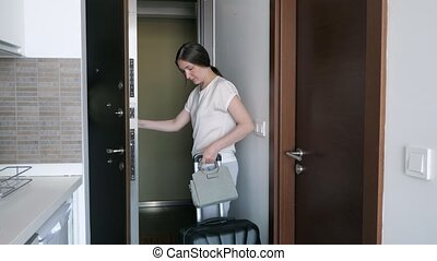 Young woman with suitcase is leaving rented apartments.