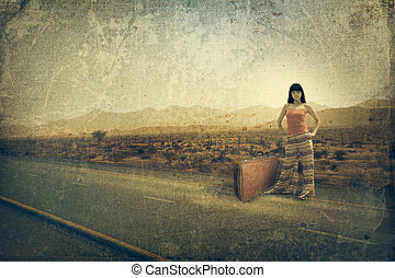 Young woman with suitcase on the road