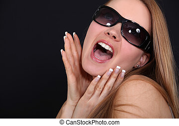 Young woman with sunglasses screaming in front of a black background