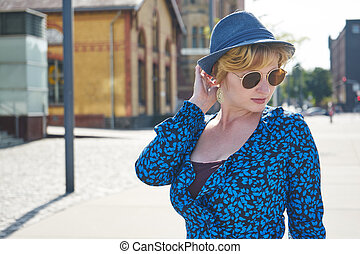 young woman with sunglasses wears blue outfit
