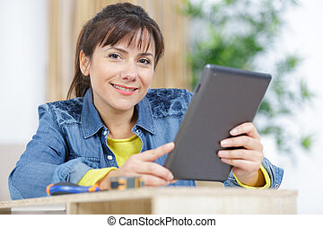 young woman with tablet in hand smiling