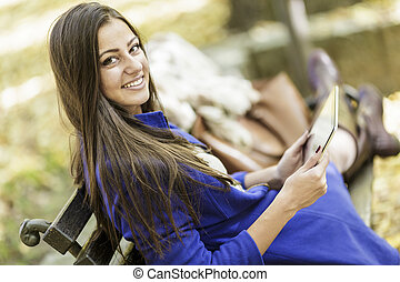 Young woman with tablet in the park
