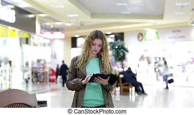 Young woman with tablet meets guy in shopping mall