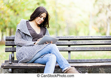 Young woman with tablet on the bench