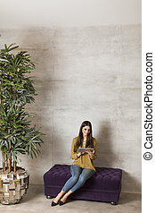 Young woman with tablet on the sofa