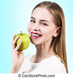 Young woman with teeth braces and green apple