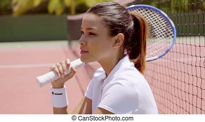 Young Woman with Tennis Racket Sitting on Court
