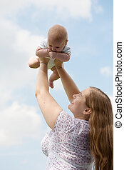 young woman with the small child against the blue sky