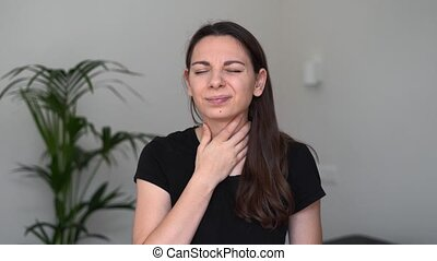 Young woman with throat sore stays at home. Influenza symptom. Seasonal flu. Covid-19 pandemic