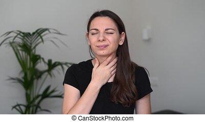 Young woman with throat sore stays at home. Influenza symptom. Seasonal flu. Covid-19