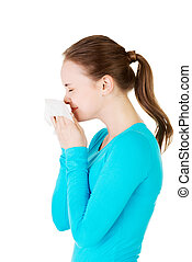 Young woman with tissue - sneezing.