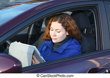 Young woman with touchpad sitting in car