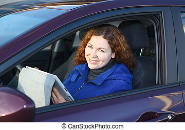Young woman with touchpad smiling in car