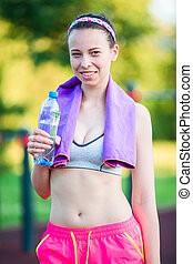Young woman with towel drinking water after running outside. Female fitness model training outside in the park. Healthy wellness fitness lifestyle.