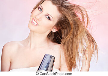 woman with towel holding blow dryer - Young woman with towel...