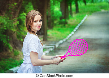 Young woman with toy badminton