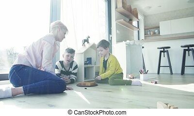 A young woman with two children playing board games on the floor. Slow motion.