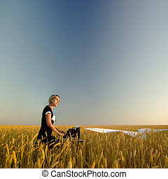 Young woman with typewriter in field of wheat - Young woman...