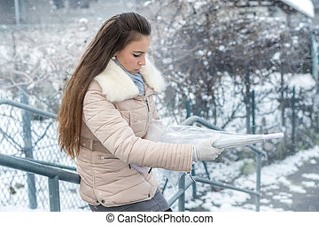 Young woman with umbrella in snowfall