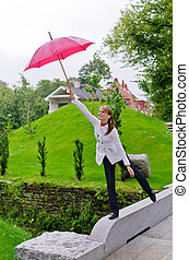 Young woman with umbrella in the park