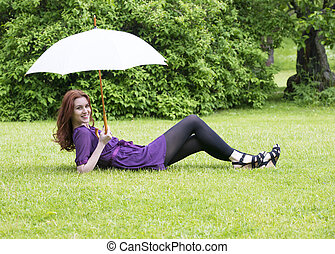 Young woman with umbrella lying in a park