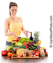 Young woman with variety of organic grocery products on white