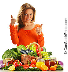 Young woman with variety of organic vegetables isolated on white background