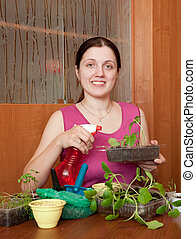 Young woman with various seedlings