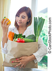 Young Woman with vegetables in shopping bag