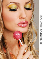 Young woman with vibrant makeup holding a lollipop
