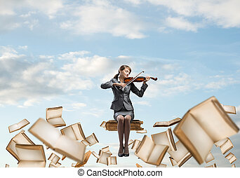 Young woman with violin sitting on big book