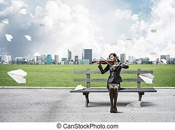 Young woman with violin sitting on wooden bench