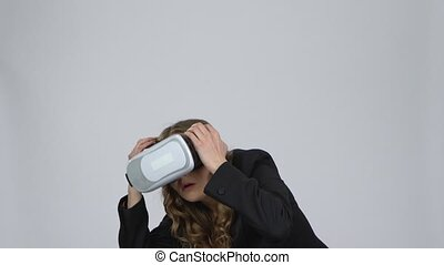 Young woman with virtual reality glasses on her head on gray background at studio.