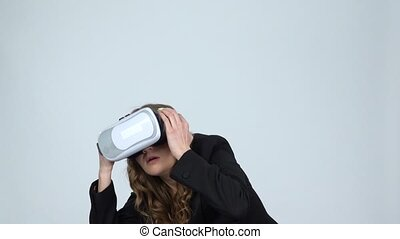 Young woman with virtual reality glasses on her head on gray background, slow motion.